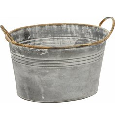 A galvanised rustic metal planter with twin handles and a distressed finish.