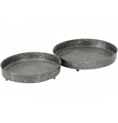 A set of 2 rustic zinc round trays with a small base.