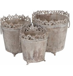 A set of 3 antique style buckets on feet. Each has twin handles and a filigree pattern. Ideal for topiary balls