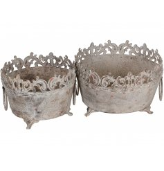 A set of 2 antique style round planters with twin handles and feet. A charming decorative item
