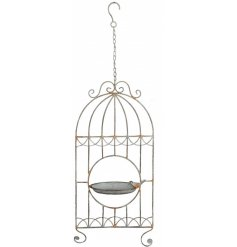 A rustic style bird feeder and bird ornament set within a decorative and distressed birdcage.