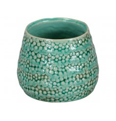 A unique green vessel with a decorative surface pattern and a rich lustre finish.
