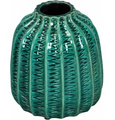 A richly coloured green vase with a ribbed texture and zig zag pattern. A stylish interior accessory.