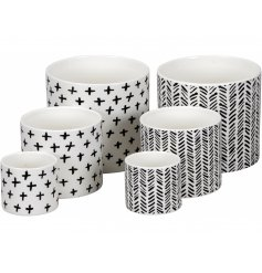 A set of 3 black and white contemporary planters, each with a graphic design.