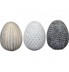 An assortment of 3 rough luxe egg ornaments in gold, cream and black colours. Each has a rustic finish