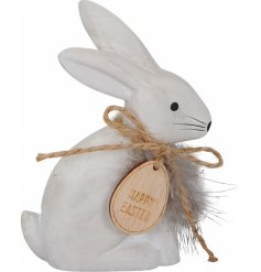 A charming little concrete bunny decorated with a twine bow, wooden tag and feather finish