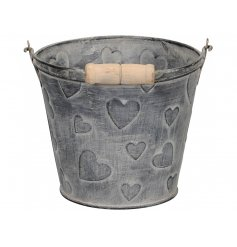 A rustic bucket with an embossed heart design and wooden handle.