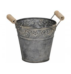 A rustic metal bucket with a floral decorative pattern and twin wooden handles.