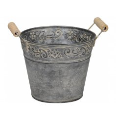A stylish rustic bucket with a floral motif and twin wooden handles.