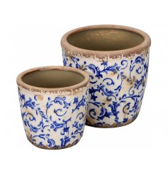A set of 2 rustic style planters with a vintage blue floral design. A lovely gift item and planter for your patio.