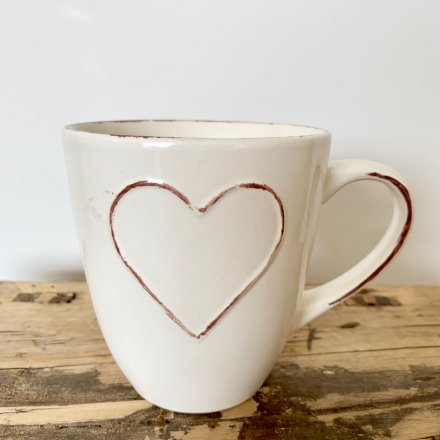 A shabby chic mug in cream. Complete with a heart design. A rustic kitchenware item which is much loved.