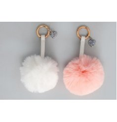An assortment of pink and white fluffy pompom key rings complete with sparkly heart decals