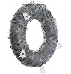 A rustic birch wreath in grey with a sprinkling of festive sparkle and white Christmas tree decorations.