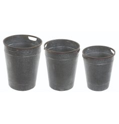 A set of 3 tall rustic metal planters with handles. A classic garden planter and rustic gift item.