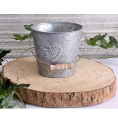 Featuring a white washed embossed heart decal and smooth zinc metal finish, this charming bucket will place perfectly i