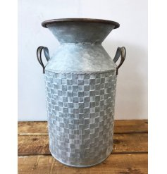 A rustic zinc metal churn with twin handles and a textured square tile pattern.