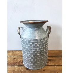 A charming zinc metal churn with a patchwork pattern and twin handles.