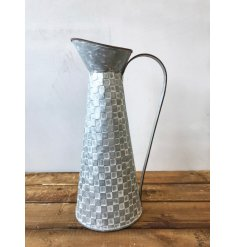 A tall and beautifully shaped metal jug with a square tile design and rustic finish.