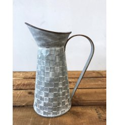 A rustic style metal jug with a textured square tile pattern.