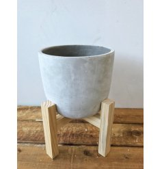 A contemporary style concrete planter on a wooden stand. A modern and unique interior accessory.