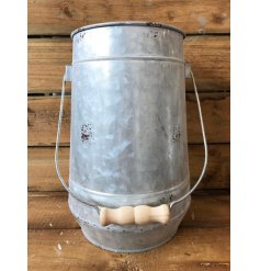 A zinc planter with a rustic finish and wooden handle. A chic decoration and planter/vase for your fresh picked blooms.