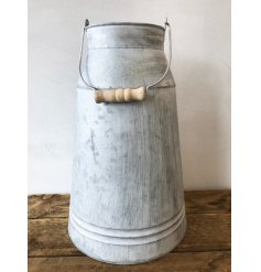 A rustic zinc churn with a wooden handle and a distressed finish.