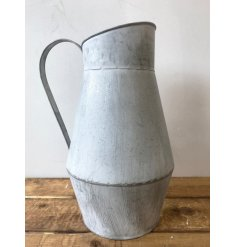 A rustic style metal jug with a distressed finish.