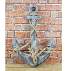 A large distressed wooden anchor with a chunky rope wrap. A beautiful coastal themed wall art.
