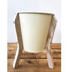 A chic and unique cream planter with a rustic wooden stand.