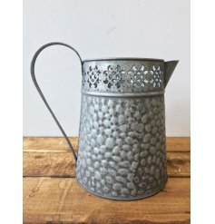 A rustic metal jug with a delicate cut out motif. A charming decoration and planter/vase for the home.