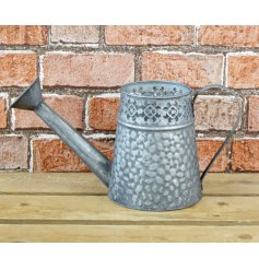 A rustic watering can with a distressed finish and decorative pattern.