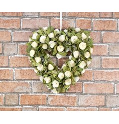 A chic heart shaped wreath with wooden flowers and green leaves. A unique interior accessory.