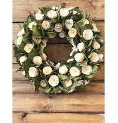 A chic wooden wreath with white roses and attractive green leaves. A beautiful decoration to be treasured and enjoyed