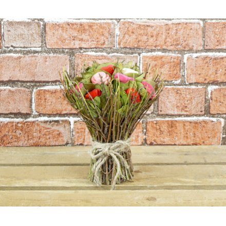 A stunning bouquet of red and pink roses encased within a natural twiggy framework.