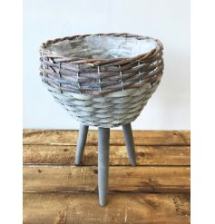 A rustic style woven willow planter with stand. A beautiful garden and interior decoration.
