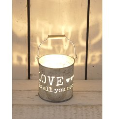 A rustic metal candle pot with wooden handle and love is all you need slogan.