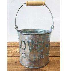 A rustic zinc pot with handle featuring a love is all you need slogan.