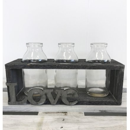 A chic and simple wooden bottle holder with a love slogan and 3 bottles.