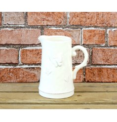 A charming cream ceramic jug with butterfly decorations.