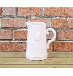 A shabby chic style ceramic jug in pink with decorative butterfly detailing. A stylish interior accessory and gift item.