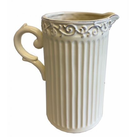 A classic cream ceramic jug with ribbed detailing and a shabby chic decorative pattern around the rim.