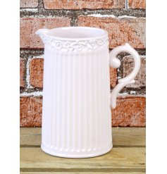 A rustic style ceramic jug in pink. A ribbed jug with a shabby chic decorative rim.