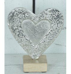 A stylish aluminium heart decoration with a hammered finish, set upon a wooden base.