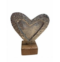A rustic style aluminium heart with a hammered finish. Set upon a wooden base. A chic gift item and interior accessory.