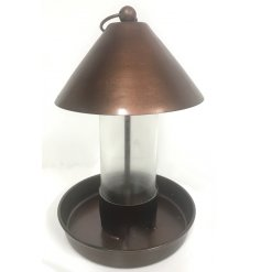 A Distressed copper toned bird feeder complete with a cone shaped top and glass surround