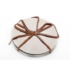 A set of 4 silver hammered coasters with a brown leather bow.