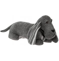 A stylish grey striped and herringbone patchwork design dog doorstop with an adorable bow.