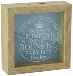 A charming wooden money box with a glass front, featuring a bouncing baby boy slogan.