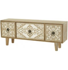 A shabby chic style wooden cabinet on legs. Each drawer has a carved decorative pattern with vintage inspired handles.