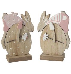 A mix of 2 wooden rabbit decorations, each draped over eggs. Decorated in pink pastel colours with polka dot detailing